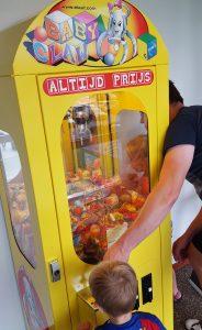 De grijpmachine waar kinderen een muntje voor krijgen na het eten.